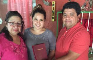 Pastors Handing Bible to Flores